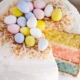 Easter Egg Layered Cake - A colorful vanilla cake topped with whipped buttercream and decorated with toasted coconut and mini Cadbury eggs. The perfect showstopper for your Easter celebration!