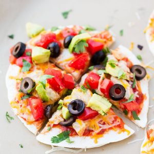 15-Minute Mexican Pizza Recipe - a dish the whole family will love! Warm tortillas stuffed with refried beans, meat, melt-y cheese and topped with salsa, tomatoes, cilantro, avocado and olives.