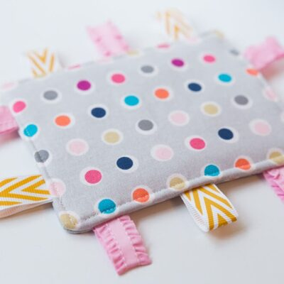 Taggie Baby Toy - a simple sewing project perfect for any new baby. Colorful ribbons and a bright pattern makes this a great sensory toy for your little one.