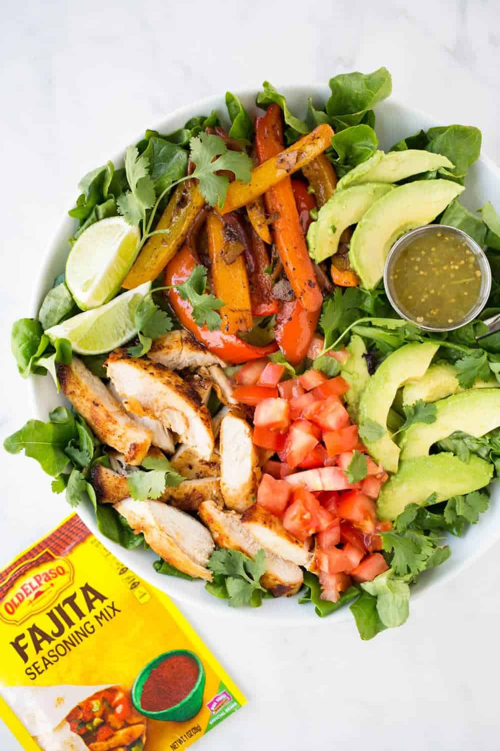 EASY Fajita salad recipe... done in 20 minutes or less. This salad is packed with flavorful chicken, veggies and green salsa. Perfect for a quick dinner or lunch!