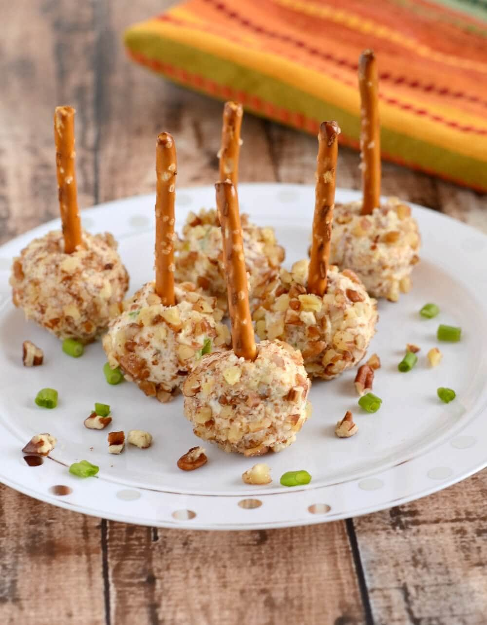 plate of mini cheese ball bites on pretzel sticks