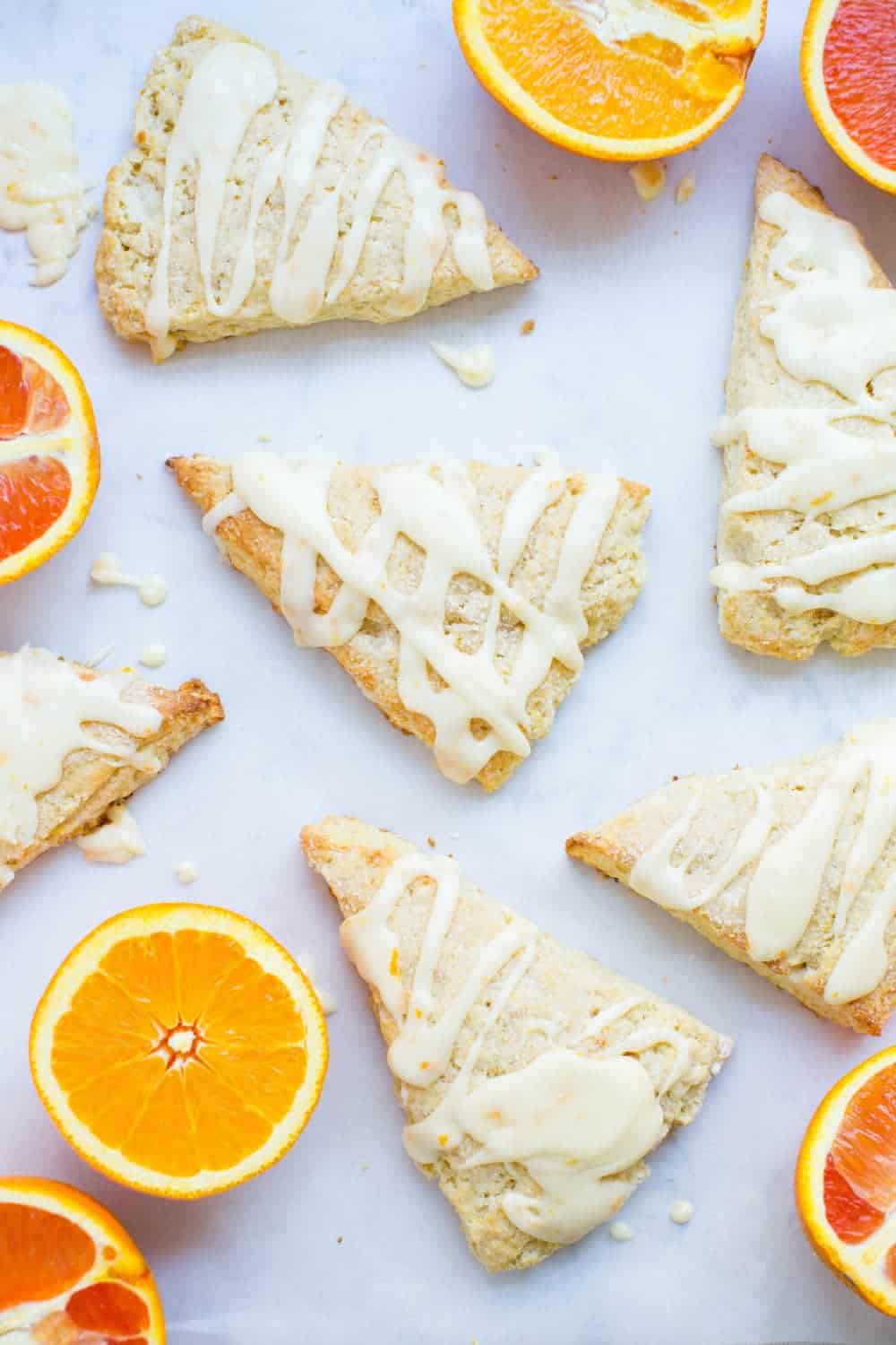 glazed orange scones on a white counter with fresh sliced oranges