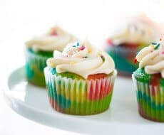 EASY rainbow cupcakes made with a doctored cake mix recipe and buttercream frosting! Everyone loved these!