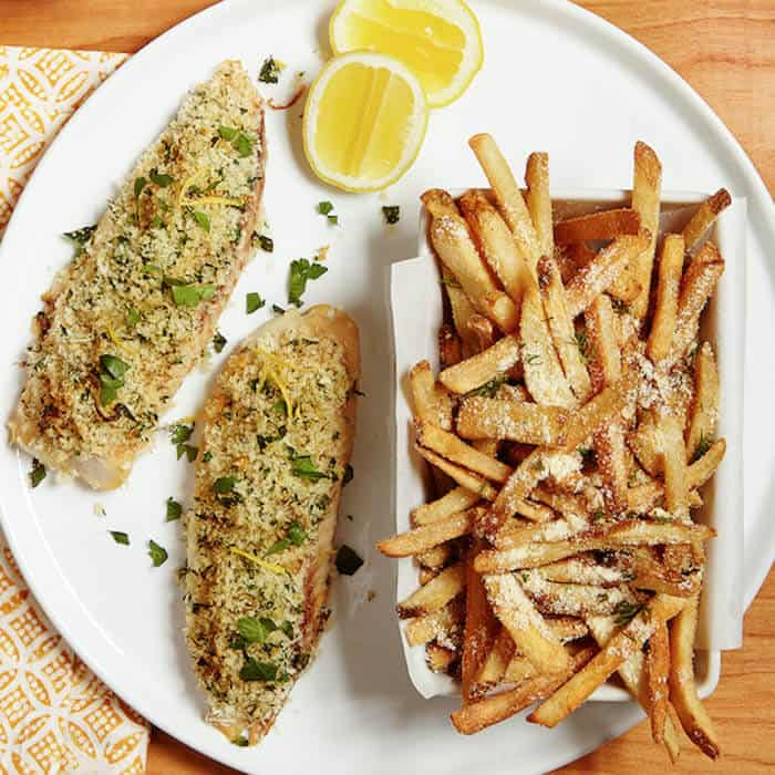 lemon baked fish on a plate with parmesan fries