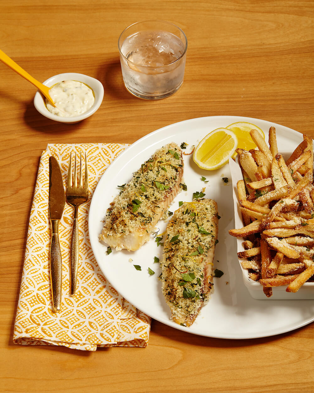 oven baked fish on a plate with crispy parmesan fries