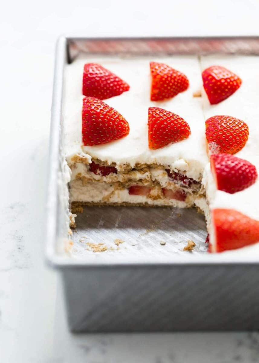 strawberry icebox cake in pan with slice taken out