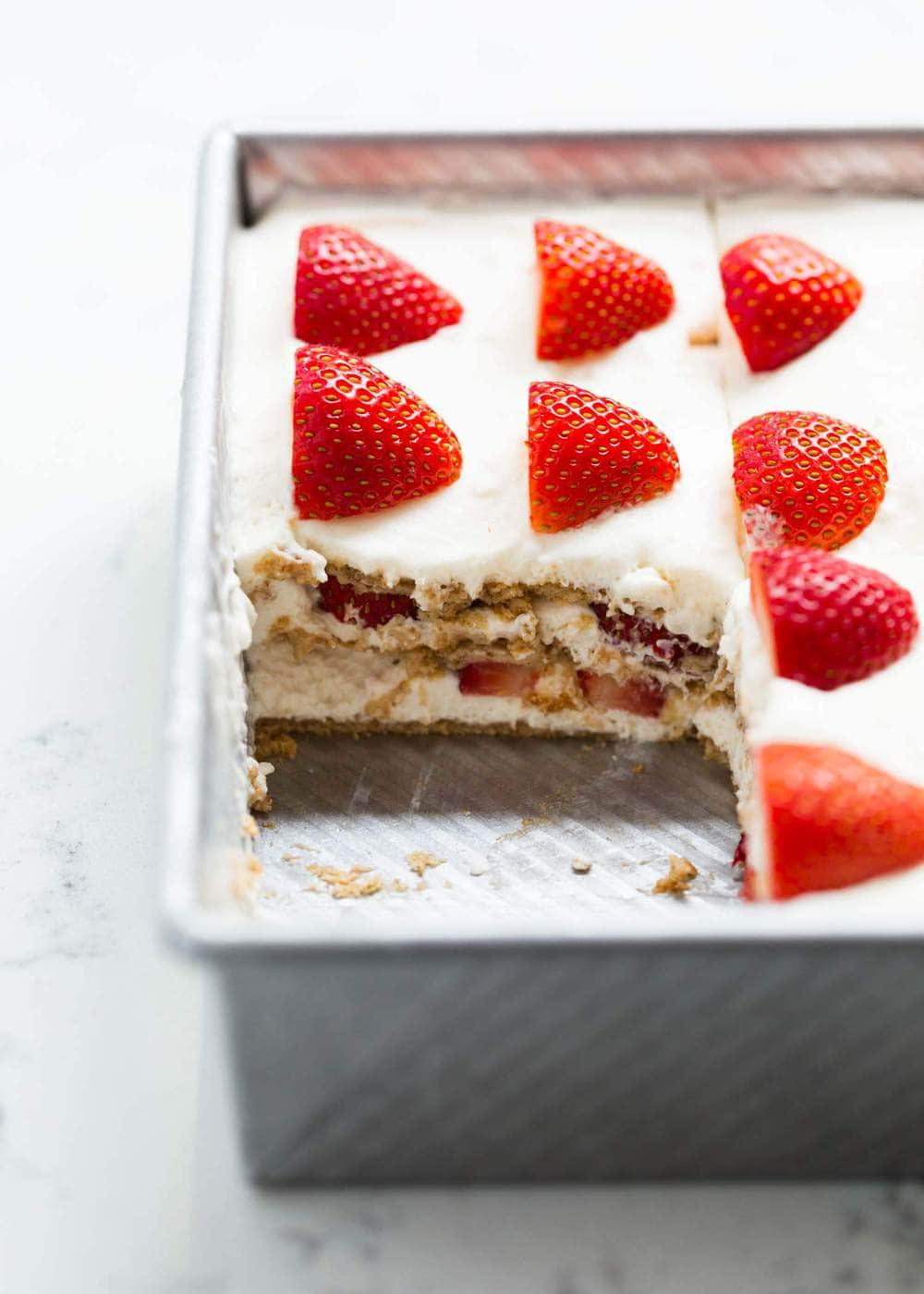 icebox cake topped with strawberries in a silver pan with one piece removed