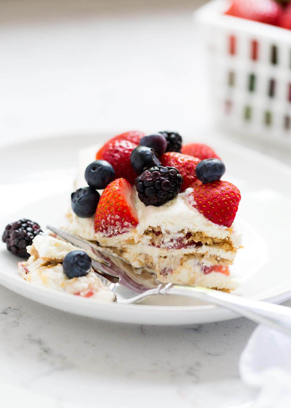 piece of strawberry icebox cake on a white plate topped with fresh berries