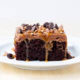 Chocolate Turtle Poke Cake recipe - filled with ooey gooey caramel and topped with even more caramel, chocolate and nuts. Super easy and delicious!