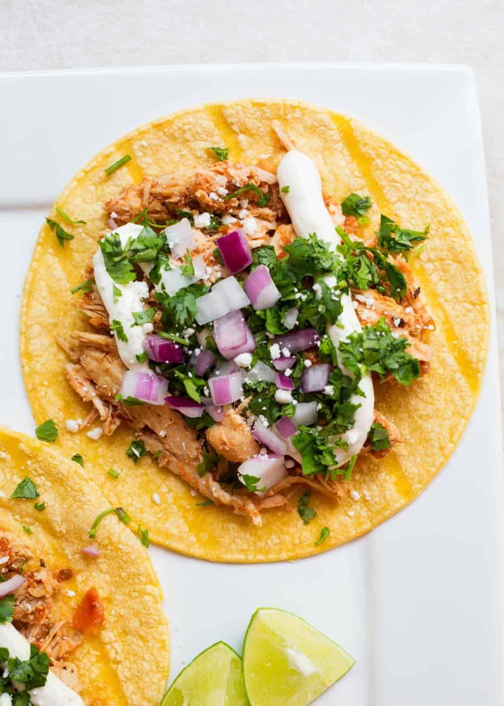 chicken tinga taco topped with crema, cilantro and red onion