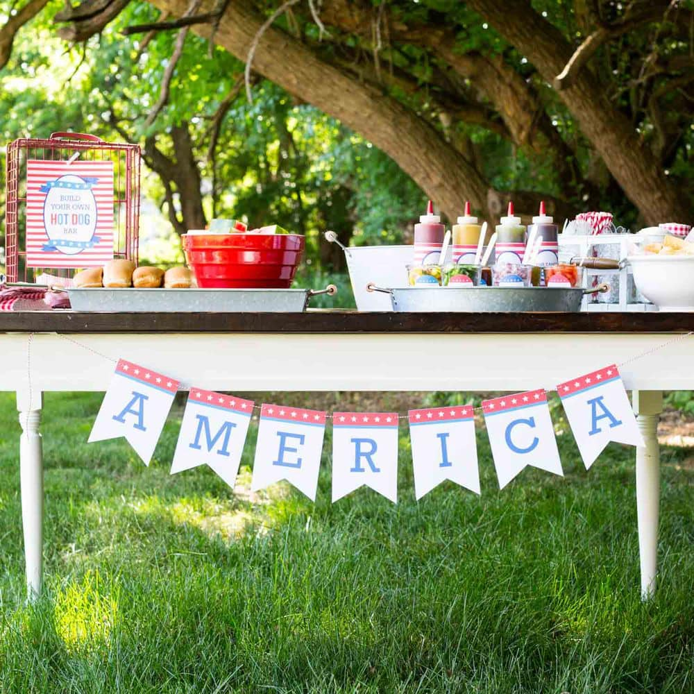 hot dog bar on a table with an america banner hanging across
