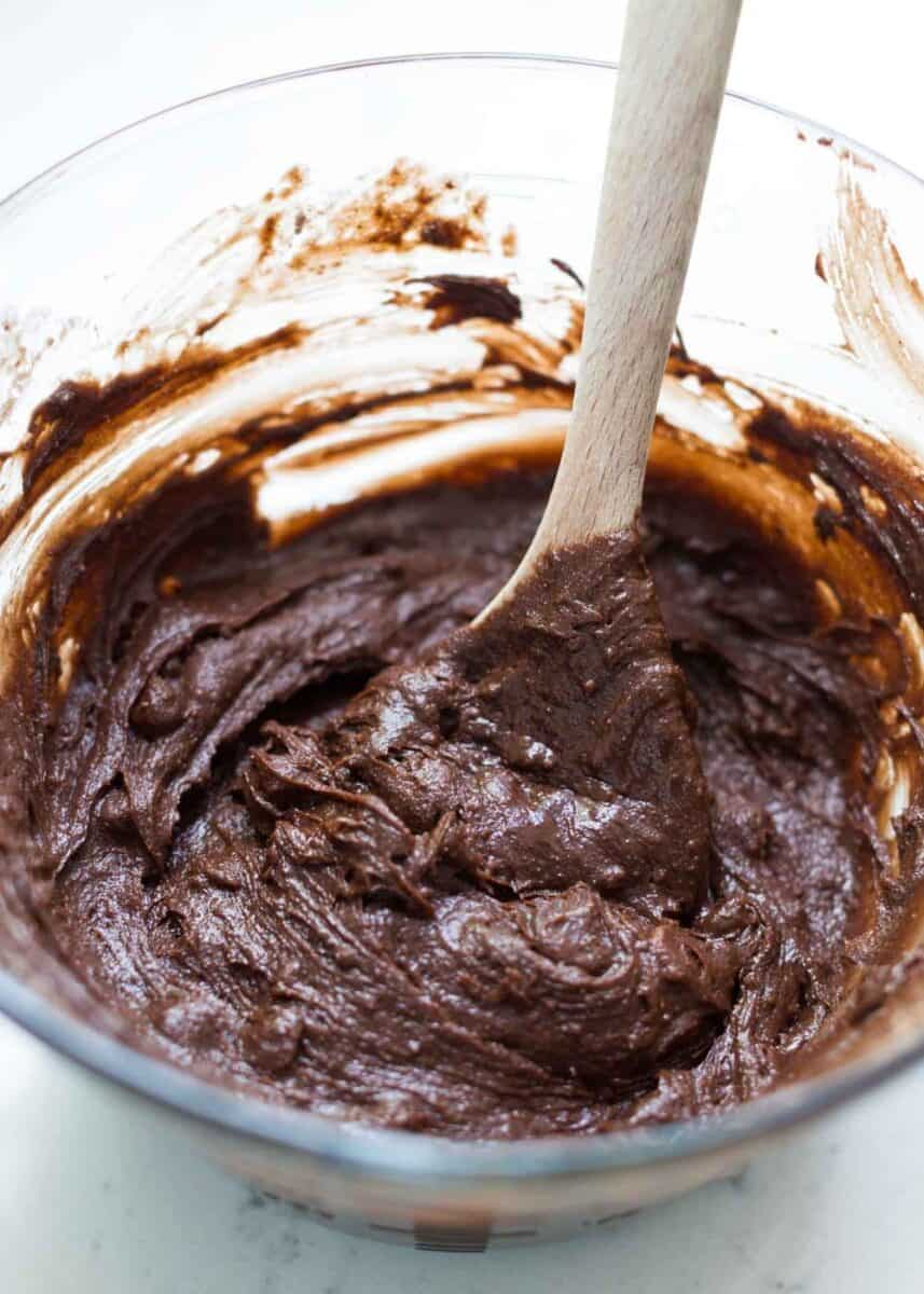 mixing brownie batter with wooden spoon