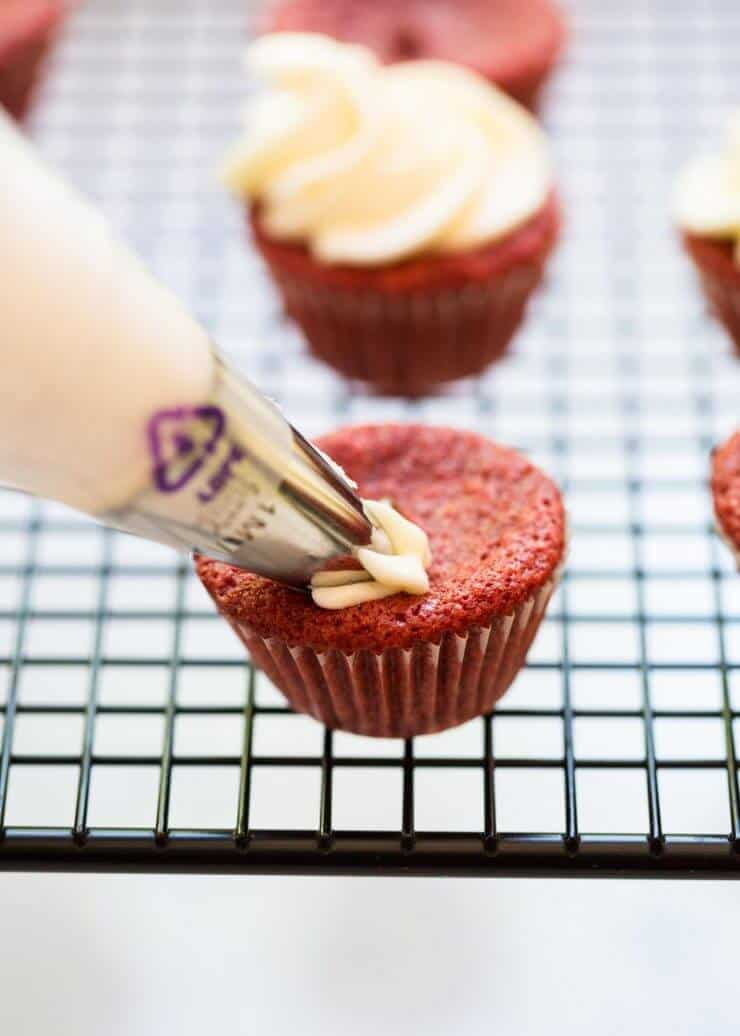 Red Velvet Brownie Cups with Cream Cheese Frosting - piping the frosting on the delicious mini cupakes