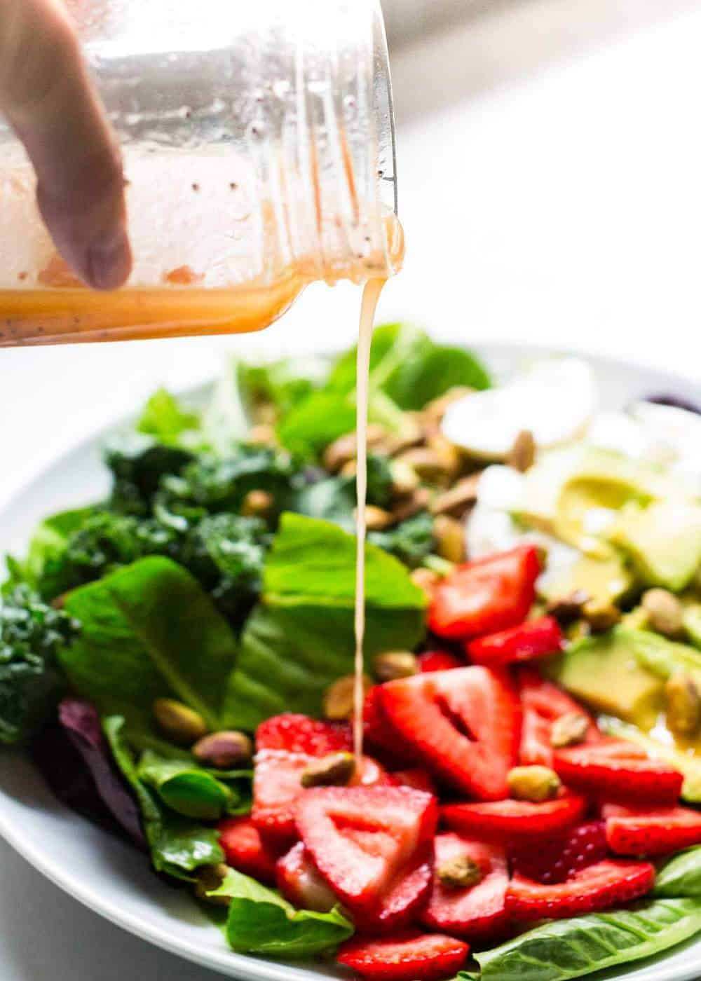 pouring poppyseed dressing over strawberry burrata salad