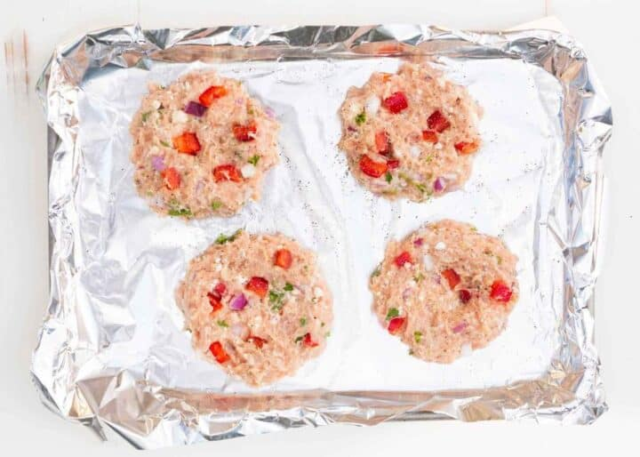 4 greek chicken burger patties on a foil lined baking sheet