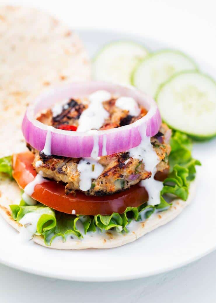 greek chicken burger on a flatbread with lettuce, tomato and onion