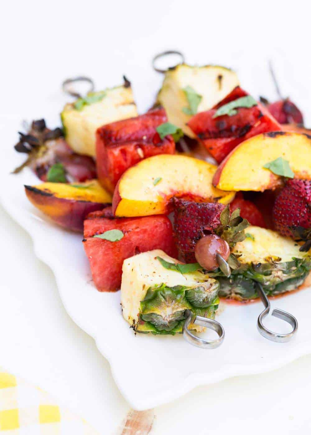 grilled fruit kabobs on a white plate