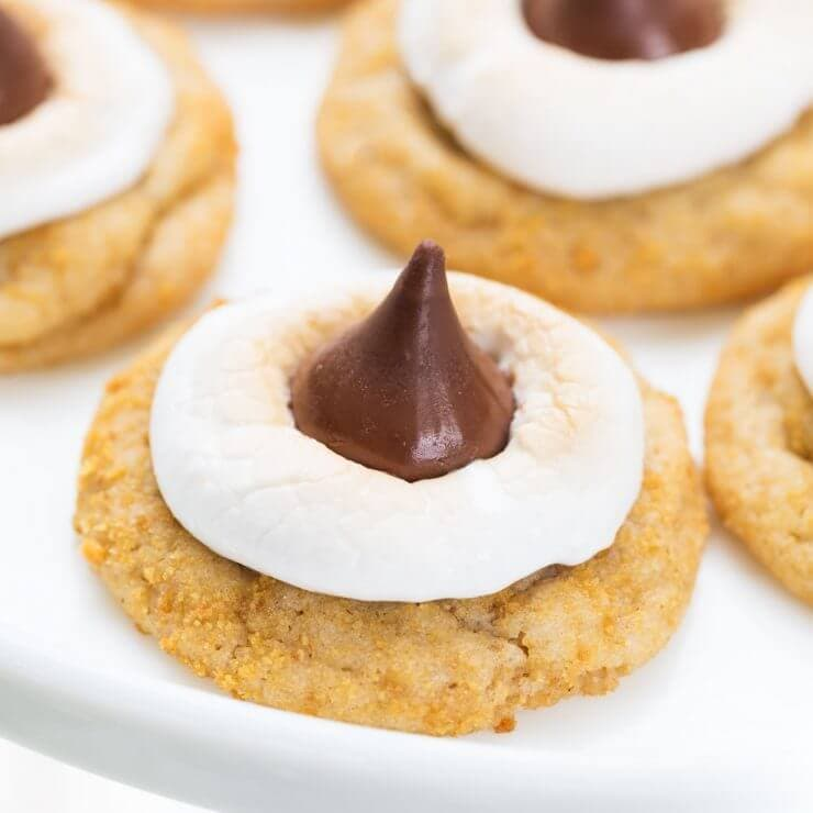 Soft and chewy s'mores cookies with a buttery graham cracker flavored dough, a gooey marshmallow and chocolate HERSHEY'S KISS on top! This summer treat is even better than the traditional s'mores and no campfire is needed!