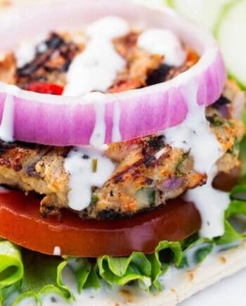 greek chicken burger with lettuce, tomato and onion