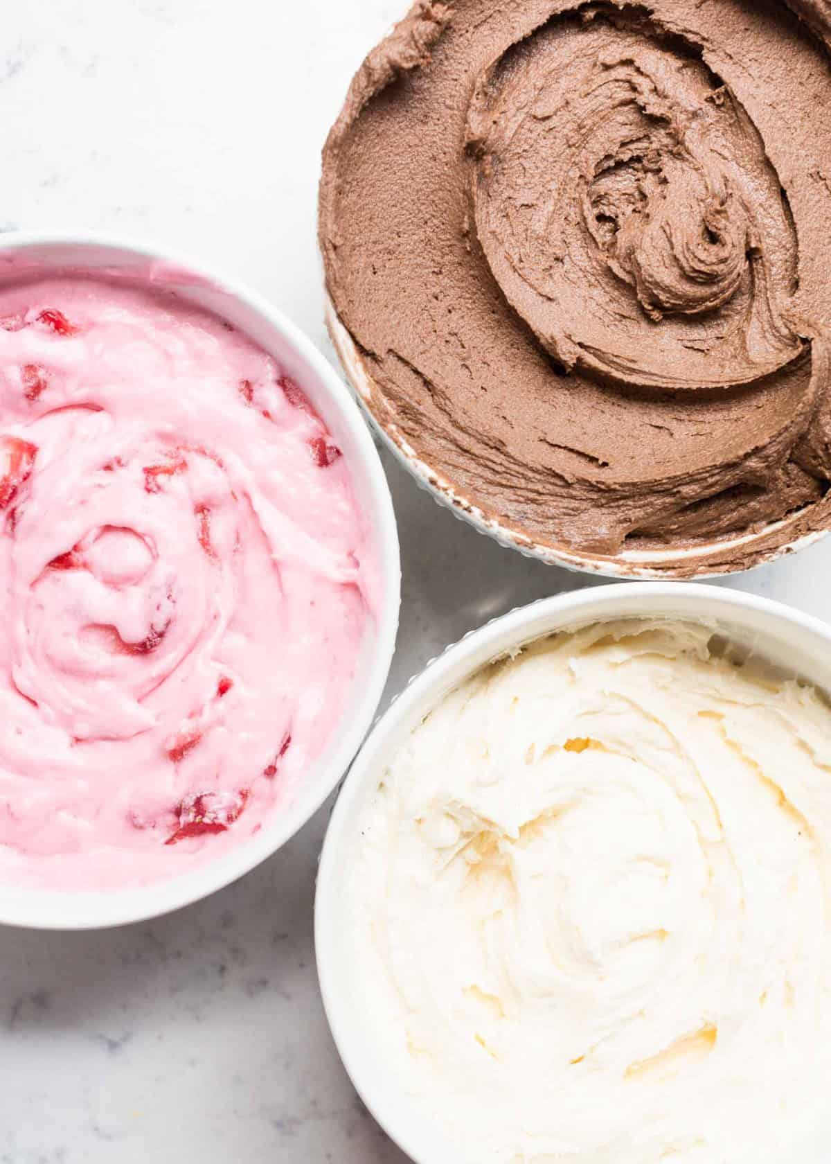3 bowls with classic, chocolate and strawberry buttercream frosting
