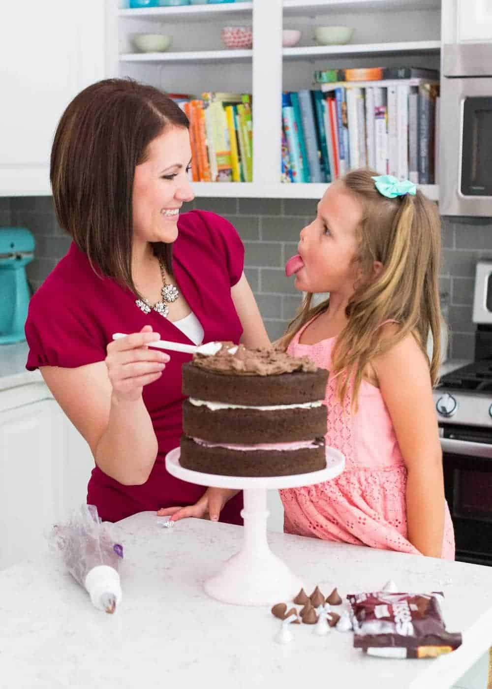 woman spreading chocolate frosting onto Neapolitan cake with daughter