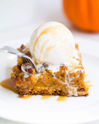 A piece of pumpkin cake on a plate with ice cream on top
