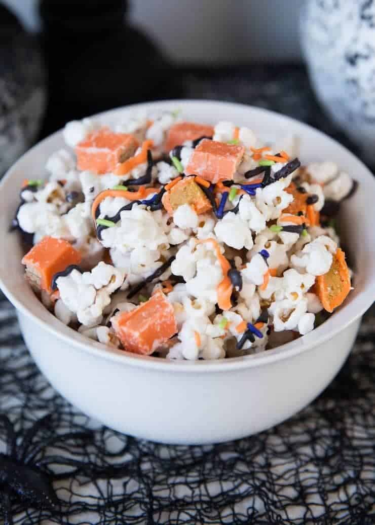 Halloween Candy Popcorn covered in white chocolate mixed with KIT KAT Bars and REESE'S! So delicious!