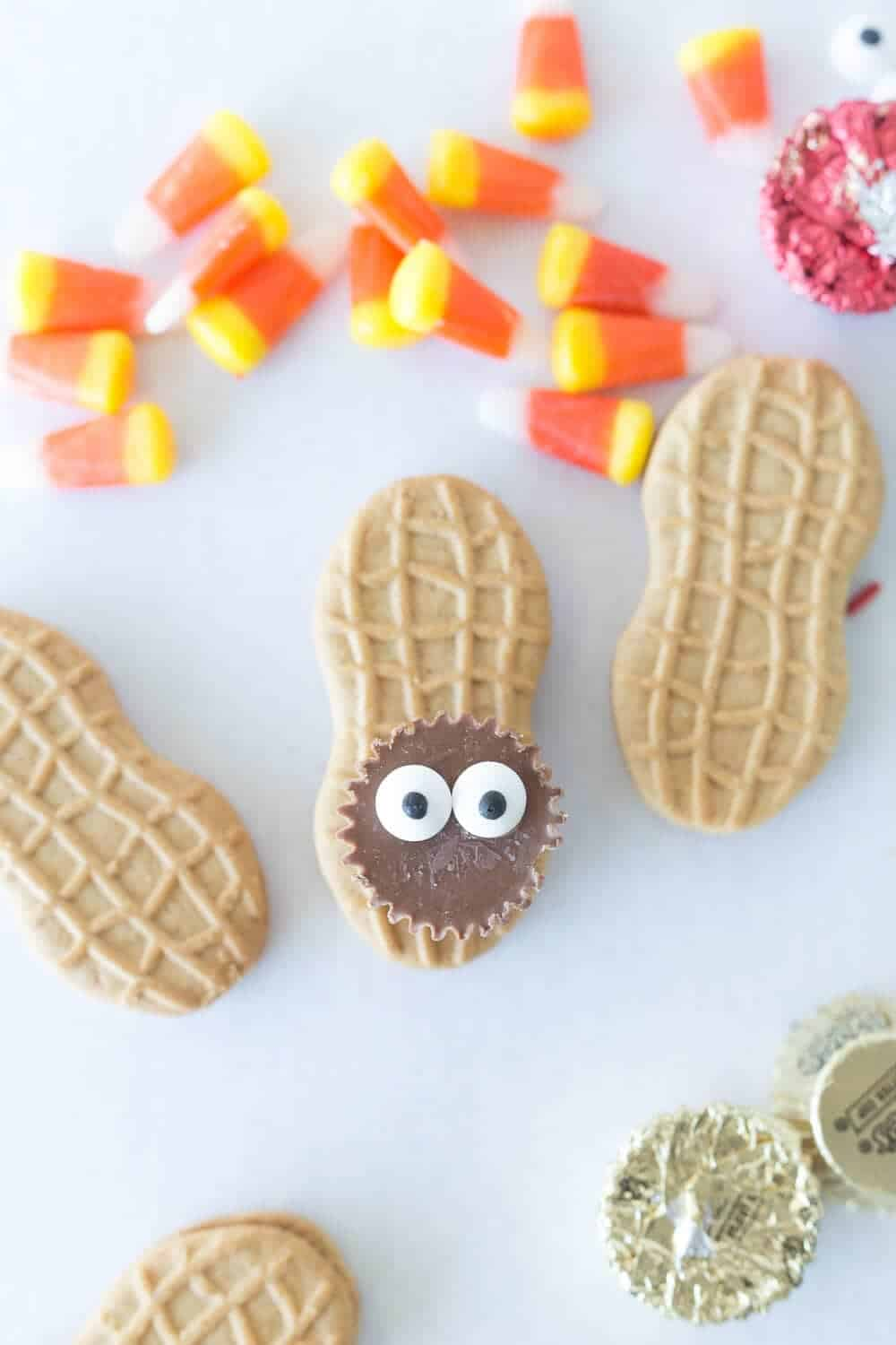 adding candy eyes on top of thanksgiving turkey cookies