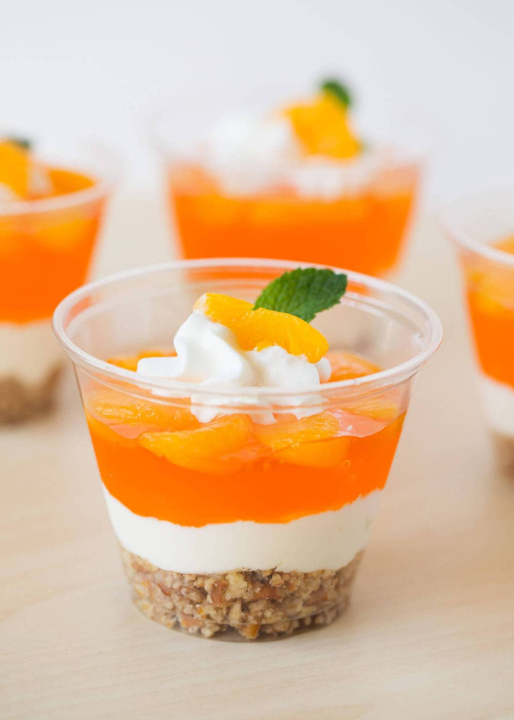 mandarin orange dessert parfait with whipped cream and a mint leaf on top