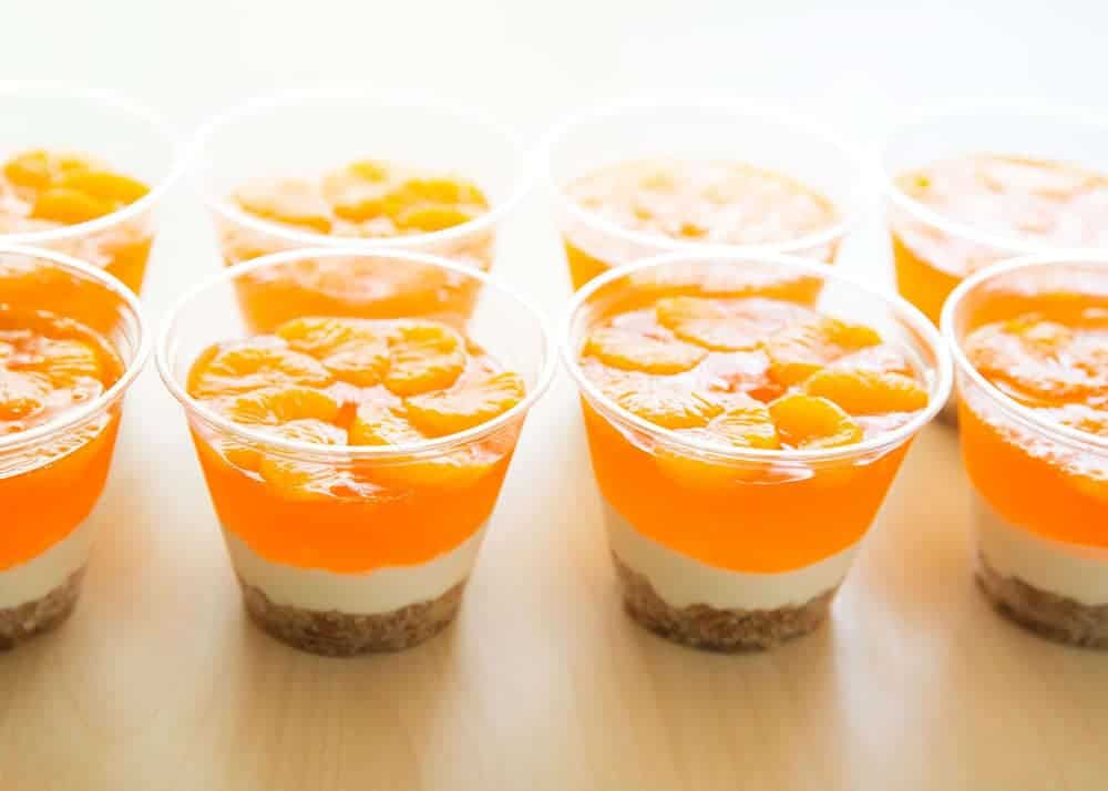 mandarin orange pretzel salad parfait cups lined up on the counter