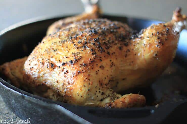 a whole roasted chicken in a cast iron skillet