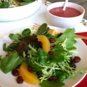 winter salad with cranberry vinaigrette on white plate