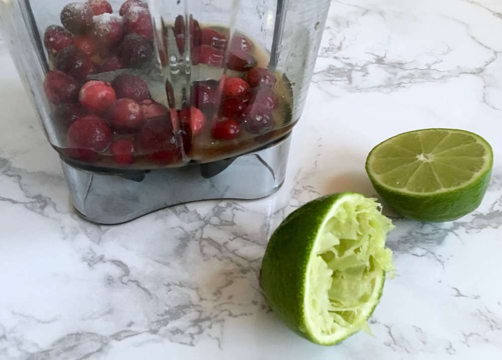 blending together cranberries and lime juice for cranberry vinaigrette