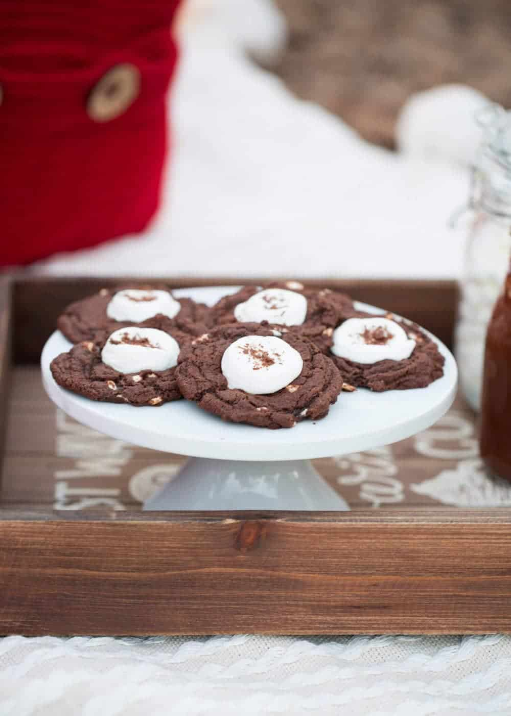 hot chocolate cookies on a white cake stand