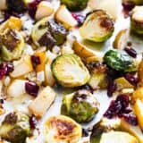 roasted brussels sprouts with cranberries and pears on baking sheet