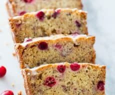 Cranberry Banana Bread... filled with white chocolate chips and topped with a powdered sugar glaze. So soft and full of flavor!