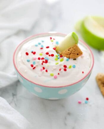 bowl of funfetti dip with an apple slice and graham cracker stick