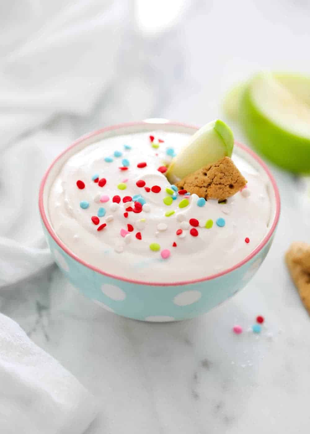bowl of funfetti dip topped with sprinkles, an apple slice and a graham cracker