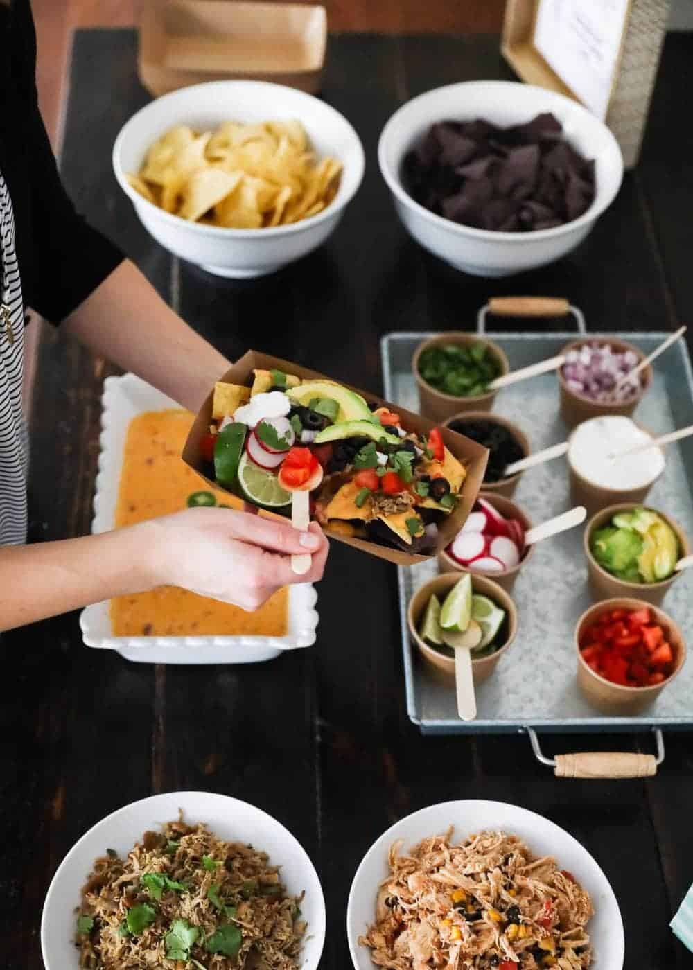 adding toppings to nachos from a nacho bar
