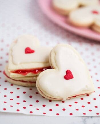Heart Shaped Empire Cookies sandwiched with a raspberry jam filling and topped with an almond glaze. The perfect Valentine's Day dessert.