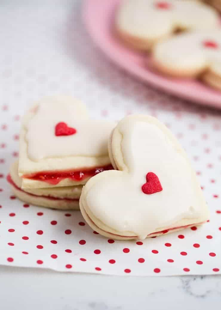 A close up of two valentine empire cookies