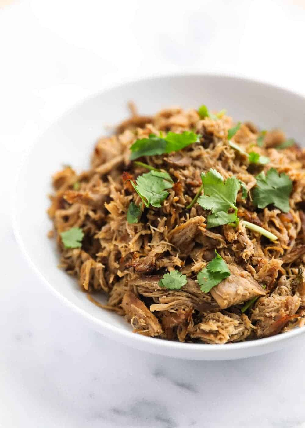 bowl of crock pot carnitas with cilantro on top