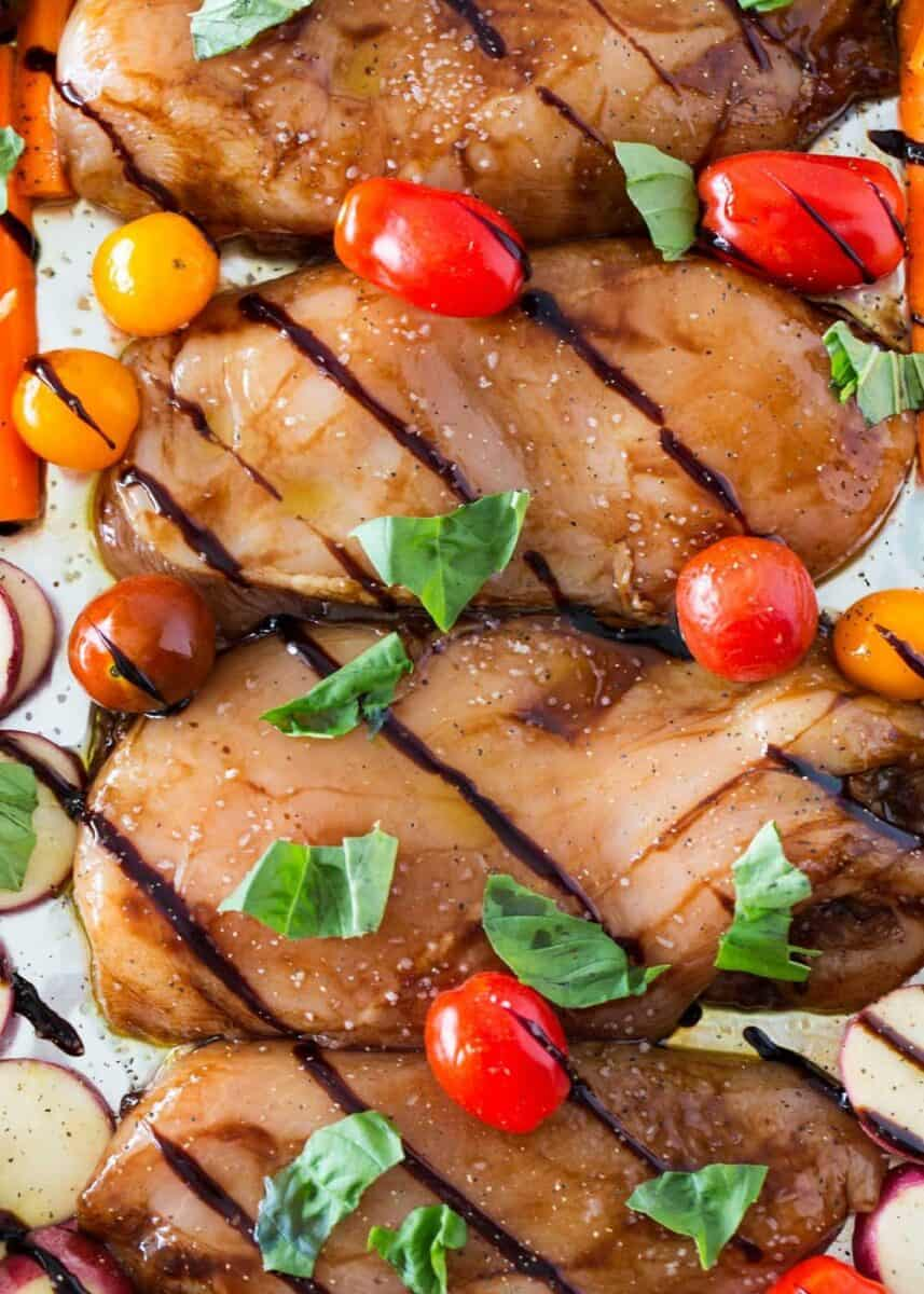 close up of balsamic chicken with cherry tomatoes and fresh basil