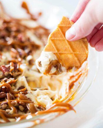 Dipping cookie into caramel pecan cheesecake dip