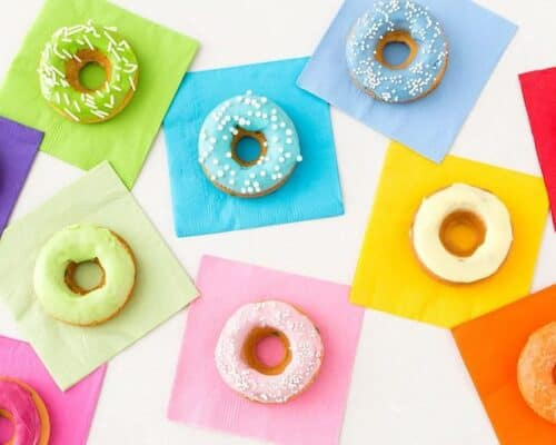 A variety of rainbow donuts on top of colorful napkins