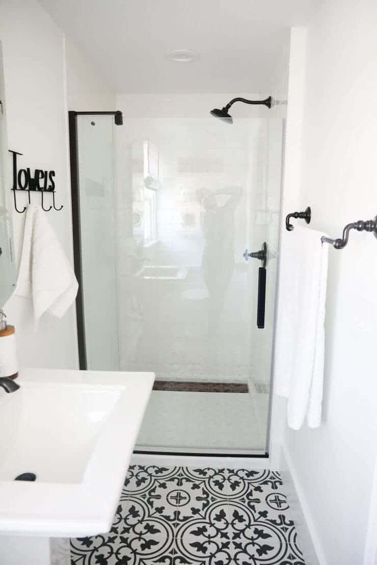 Black and white bathroom makeover on a 1888 fixer upper: white subway tile, oil rubbed bronze finishes + cement tile