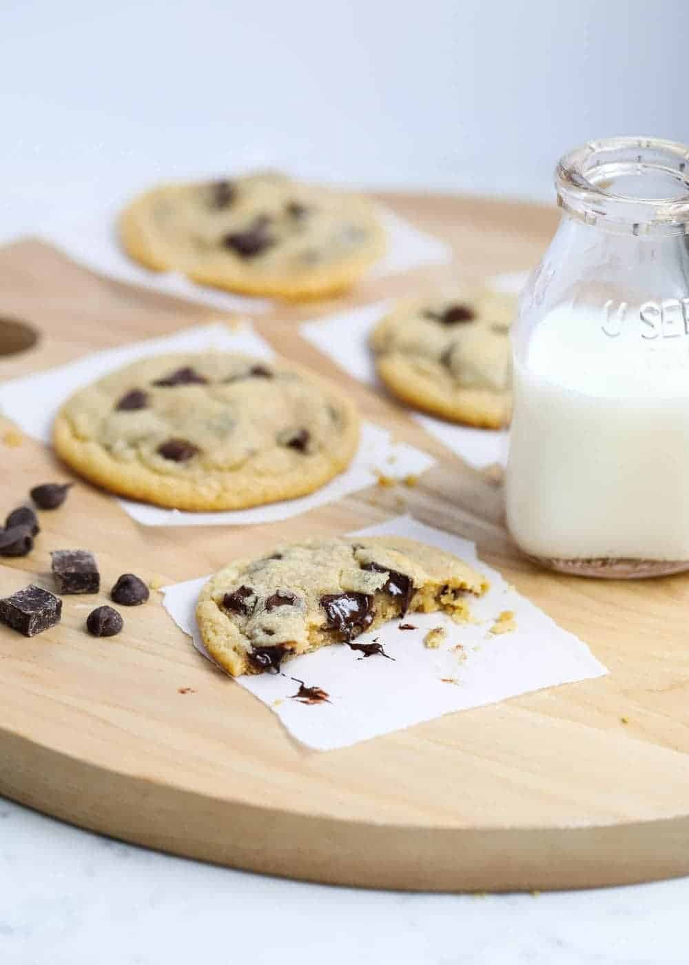 brown butter cookies on a wood plank with a glass of milk