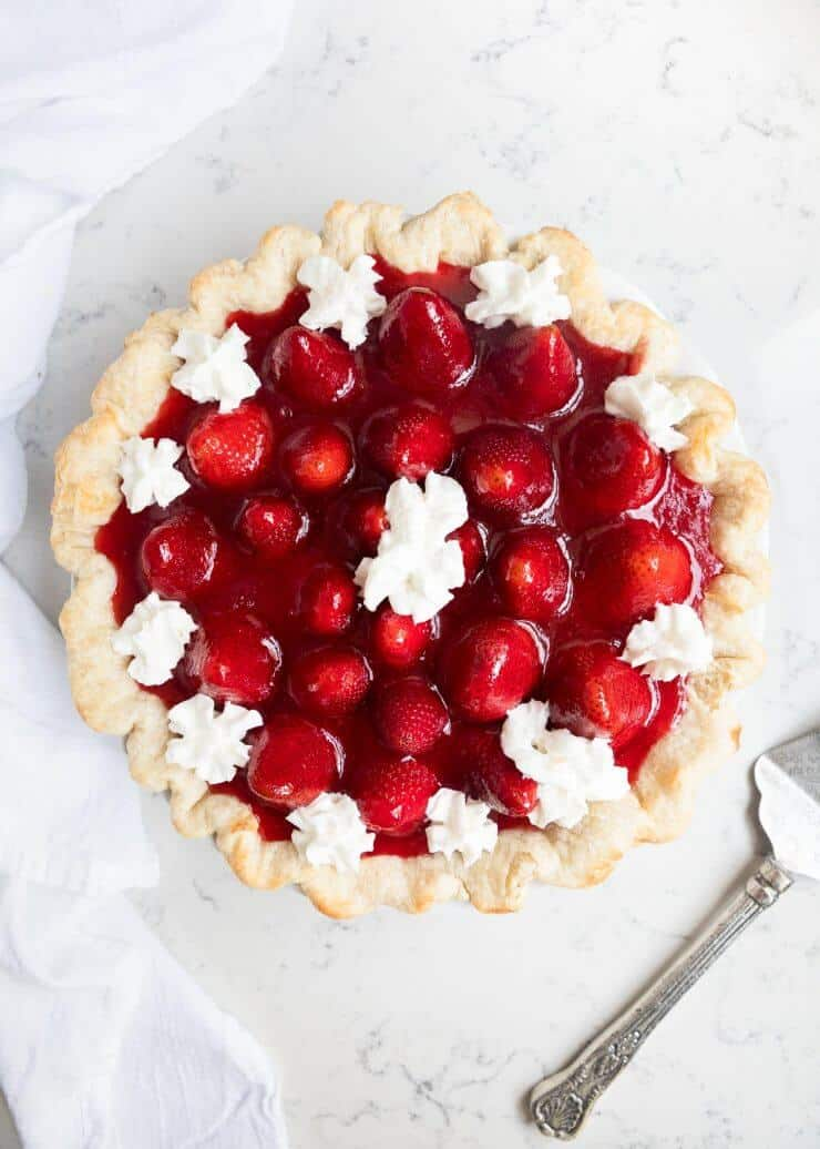 strawberry cream pie with dollops of whipped cream on top