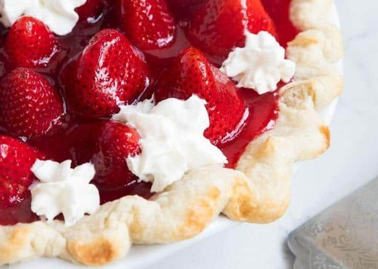 close up of fresh strawberry pie with whipped cream