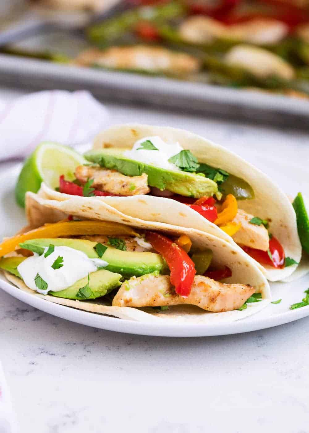 plate of chicken fajitas in tortillas